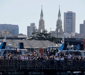 In this Sept. 18, 2013, file photo, spectators at Pier 39 watch Emirates Team New Zealand and Oracle Team USA during the 11th race of the America's Cup sailing event in San Francisco. (AP Photo/Eric Risberg, File)