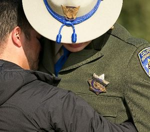 A black band covers the badge of California Highway Patrol Officer Jonathan Velazquez as he is comforted following a bell ringing ceremony held for CHP Officer Andrew Camilleri Sr., at the highway patrol academy Wednesday, Dec. 27, 2017, in West Sacramento, Calif. (AP Photo/Rich Pedroncelli)
