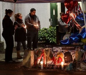 Visitors hold candles as they view a growing memorial to slain sheriff's deputy Daniel McCartney, Monday, Jan. 8, 2018, at the South Precinct headquarters of the Pierce County Sheriff's Dept. (AP Photo/Ted S. Warren)
