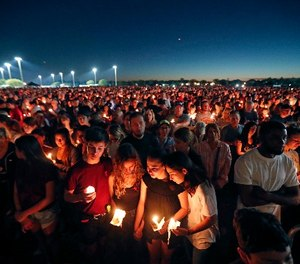 People attend a candlelight vigil for the victims of the Wednesday shooting at Marjory Stoneman Douglas High School, in Parkland, Fla., Thursday, Feb. 15, 2018. (AP Photo/Gerald Herbert)