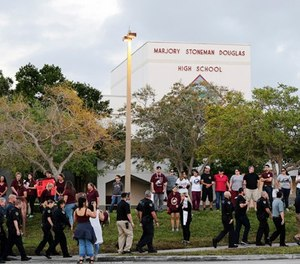 Police walk outside Marjory Stoneman Douglas High School in Parkland, Fla., Wednesday, Feb. 28, 2018. (AP Photo/Terry Renna)