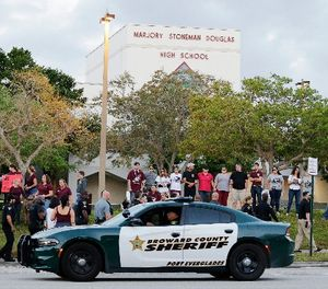 A police car drives by Marjory Stoneman Douglas High School in Parkland, Fla., Wednesday, Feb. 28, 2018. (AP Photo/Terry Renna)