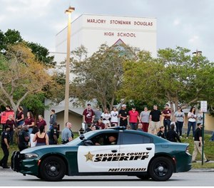 A patrol car drives by Marjory Stoneman Douglas High School in Parkland, Fla., Wednesday, Feb. 28, 2018. (AP Photo/Terry Renna)