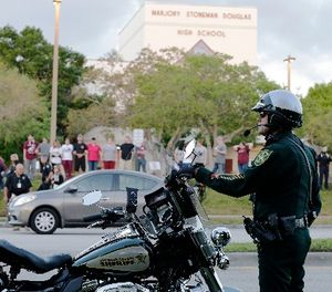 A police officer stands watch at Marjory Stoneman Douglas High School in Parkland, Fla., Wednesday, Feb. 28, 2018. (AP Photo/Terry Renna)