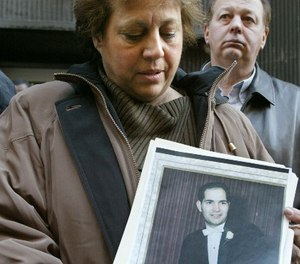 In this Jan. 9, 2004 file photo, Diane Piagentini, widow of slain police officer Joseph Piagentini, holds a photo of her husband from their wedding day in 1966, after a parole hearing in New York. (AP Photo/Diane Bondareff, File)