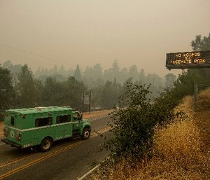 A fire transport drives along Highway 140, one of the entrances to Yosemite National Park, on Monday, July 16, 2018, in Mariposa, Calif. The road remains closed as crews battle a deadly wildfire burning near the west end of Yosemite National Park. (AP Photo/Noah Berger)