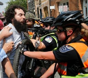 A demonstrator confronts police on the anniversary of the Unite the Right rally in Charlottesville, Va., Sunday, Aug. 12, 2018. (AP Photo/Steve Helber)