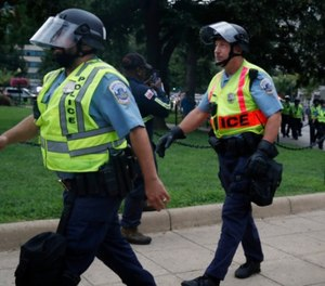 "Washington Metropolitan Police in riot gear walk near the White House on the one year anniversary of the Charlottesville ""Unite the Right"" rally, Sunday, Aug. 12, 2018, in Washington. (AP Photo/Jacquelyn Martin)"