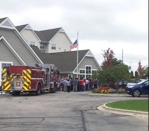 A fire truck and people evacuated are gathered at a hotel near the scene after a shooting was reported at a software company in Middleton, Wis., Wednesday, Sept. 19, 2018. Multiple were reported to have been shot. (AP Photo/Todd Richmond)