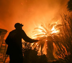 Park Billow, 27, sprays water on the hot spots in his backyard as the Woolsey Fire burns in Malibu, Calif., Friday, Nov. 9, 2018. Authorities announced Friday that a quarter of a million people are under evacuation orders as wind-whipped flames rage through scenic areas west of Los Angeles and burn toward the sea. (AP Photo/Ringo H.W. Chiu)
