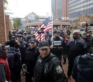 "Activist who gave his name as Jersey walks with others under police escort after a ""We The People"" rally Saturday Nov. 17, 2018, in Philadelphia. (AP Photo/Jacqueline Larma)"