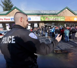 A Kirkland police officer directs traffic past a shop where Byron Ragland and local civil rights leaders addressed media members Tuesday, Nov. 20, 2018, in Kirkland, Wash. The police department there has apologized for an incident in which officers helped the owner of the Menchie's shop expel Ragland, an African-American man, from the business because employees said they felt uncomfortable. (AP Photo/Elaine Thompson)
