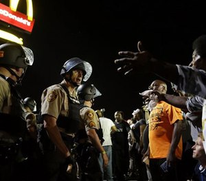 Officers and protesters face off along West Florissant Avenue, Monday, Aug. 10, 2015, in Ferguson, Mo. (AP Image)