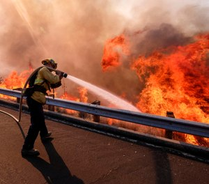 In this Nov. 12, 2018 file photo a firefighter battles a fire along the Ronald Reagan Freeway, aka state Highway 118, in Simi Valley, Calif. (AP Photo/Ringo H.W. Chiu, File)