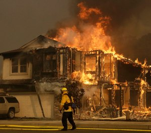 A firefighter walks near a flaming house in Santa Rosa, Calif. Investigators say the deadly 2017 wildfire that killed 22 people in California's wine country was caused by a private electrical system, not embattled Pacific Gas & Electric Co.  (AP Photo/Jeff Chiu)