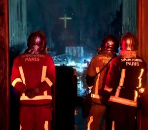 In this image taken from France Televisions video, firefighters stand at an entrance and look at the fire damage inside the Notre Dame cathedral in Paris, Monday April 15, 2019. Firefighters declared success Tuesday morning in an over 12-hour battle to extinguish an inferno engulfing Paris' iconic Notre Dame cathedral that claimed its spire and roof, but spared its bell towers. (France Televisions via AP)