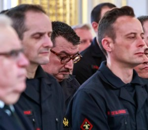 Paris fire brigade chaplain priest Jean-Marc Fournier, center bowing, listens to French President Emmanuel Macron addressing Paris Firefighters' brigade and security forces who took part at the fire extinguishing operations of the Notre Dame of Paris Cathedral fire, at the Elysee Palace in Paris, Thursday, April 18, 2019. (Christophe Petit Tesson, Pool via AP)