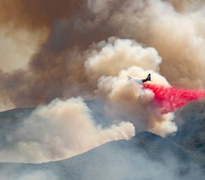 A plane drops fire retardant on a hillside in an attempt to box in flames from a wildfire during the Sand Fire in Rumsey, Calif. (Photo/AP by Josh Edelson)