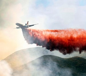 A plane drops fire retardant on a hillside in an attempt to box in flames from a wildfire during the Sand Fire in Rumsey, Calif. (AP Photo/Josh Edelson)