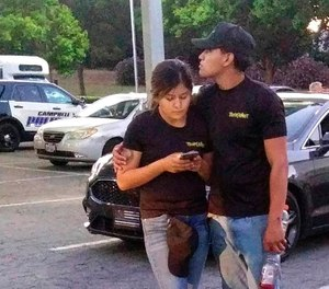 A young couple embrace at a parking lot after a shooting at the Gilroy Garlic Festival in Gilroy, Calif., Sunday, July 28, 2019. Several people were hospitalized Sunday after the shooting at the annual food festival in Northern California, a hospital spokeswoman said. (AP Photo/Thomas Mendoza)