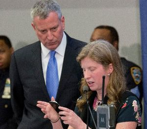 New York City Mayor Bill de Blasio, left, joins NYPD Deputy Commissioner of Information Technology Jessica Tisch as she uses a smart phone to gather information to answer a reporters question during a news conference, Tuesday, Feb. 23, 2016, at police headquarters in New York. (AP Photo/Mary Altaffer)
