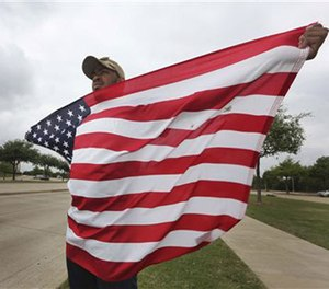 Joseph Offutt, 20, holds a U.S. flag across the street from the Curtis Culwell Center, Tuesday, May 5, 2015, in Garland, Texas. (AP Image)
