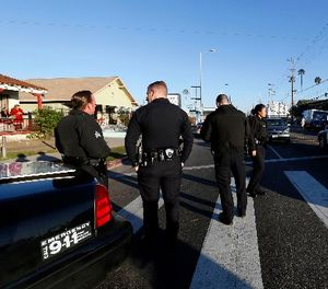 Los Angeles police officers investigate a shooting in South Central Los Angles on Monday, Dec. 29, 2014. (AP Photo/Nick Ut)