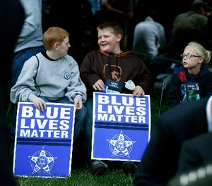 """Two boys hold signs that say """"Blue Lives Matter,"""" before the National Law Enforcement Officers Memorial Fund's Annual Candlelight Vigil, Wednesday, May 13, 2015 in Washington. (AP Photo/Alex Brandon)"""