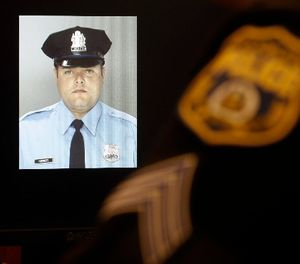 An officer sits next to a displayed image of Officer Jesse Hartnett ahead of a news conference Friday, Jan. 8, 2016, in Philadelphia. (AP Photo/Matt Rourke)