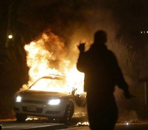 In this Nov. 24, 2014 file photo, a police car is set on fire after the announcement of the grand jury decision in the shooting of Michael Brown in Ferguson, Mo. (AP Image)