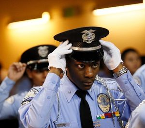 An LAPD Cadet Commander adjusts his hat before the LAPD Cadet Program Graduation. (Danny Moloshok/AP Images for The Ray Charles Foundation)