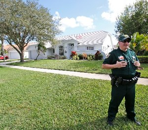 A Palm Beach County Sheriff's deputy keeps watch over the home of Palm Beach Gardens police Officer Nouman Raja, Wednesday, Oct. 21, 2015, in Lake Worth, Fla. (AP Photo/Wilfredo Lee)