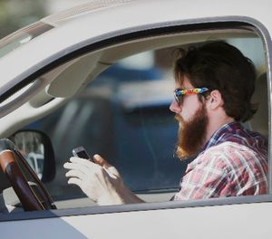 In this Feb. 26, 2013 file photo, a man uses his cell phone as he drives through traffic. (AP Photo/LM Otero)