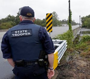 A state trooper keeps an eye on water levels at the Lamar Nathaniel Johnson bridge over the Black River Swamp in Kingstree, S.C., Monday, Oct. 5, 2015. (AP Photo/Gerry Broome)
