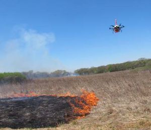 A drone designed to ignite controlled grass fires comes in for a landing in a field. (AP Photo/Grant Schulte)