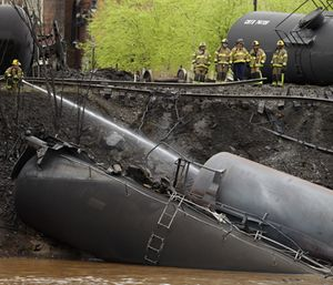 Firefighters and rescue workers work along the tracks where several CSX tanker cars carrying crude oil derailed and caught fire along the James River near downtown in Lynchburg, Va. (AP Photo/Steve Helber)