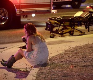 A woman sits on a curb at the scene of a shooting outside of a music festival along the Las Vegas Strip, Monday, Oct. 2, 2017, in Las Vegas. Multiple victims were being transported to hospitals after a shooting late Sunday at a music festival on the Las Vegas Strip. (AP Photo/John Locher)