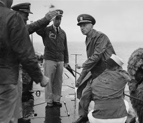 Rear Admiral Hyman G. Rickover, father of nuclear powered submarines, boards the USS Nautilus from the Navy Tug 534 in the Narrows below Brooklyn, New York on August 25, 1958. Cdr. William Anderson, head showing at left, awaits to greet the admiral aboard the U.S. Navy's first nuclear sub. Anderson is skipper of the Nautilus. Saluting at left center is Lt. Donald P. Hall, gunnery officer of the Nautilus. The craft returned earlier from four-month voyage. (AP Photo/Pool)