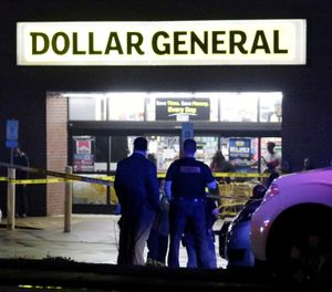 Law enforcement officers surround the Dollar General parking lot, located in the 1100 block of Opelika Road in Auburn, Ala, on Friday, Feb. 15, 2019. The site is the location of where an Auburn police officer was shot that afternoon after stopping a suspect vehicle in an attempted robbery case. (Emily Enfinger/Opelika-Auburn News via AP)