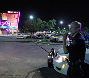 An Aurora police officer talks on his radio outside the Century 16 movie theatre in Aurora (Colo.) on July 20, 2012 during the chaotic response to the mass shooting there. (AP Photo)