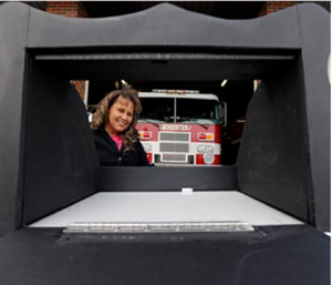 Monica Kelsey, firefighter and medic who is president of Safe Haven Baby Boxes Inc., poses with a prototype of a baby box, outside her fire station in Woodburn, Ind. (AP Photo/Michael Conroy)