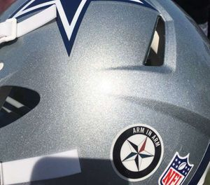 "An ""arm in arm"" decal is affixed to a Dallas Cowboys helmet at the NFL football team's training camp Saturday, July 30, 2016, in Oxnard, Calif. The Cowboys will wear the decal during preseason games, and possibly during the regular season. (AP Photo/Schuyler Dixon)"