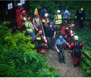 Rescued people exit Hidden River Cave after officials said over a dozen people who exploring the cave were trapped by rising water. (Austin Anthony/Daily News via AP)