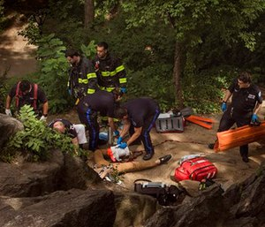 A man, center bottom, bleeds from his injured leg as he gets helped from paramedics in Central Park in New York. (AP Photo/Andres Kudacki)