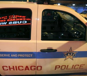 Wrigley Field's marquee message Cub Win is reflected in the window of a Chicago police department vehicle outside the stadium in Chicago  (AP Photo/Charles Rex Arbogast)