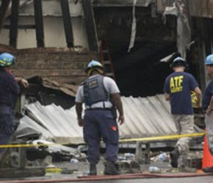 Federal investigators look over the scene after the Charleston fire. (Photo AP/Stephen Morton)