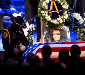 "a picture of slain Newman Police Cpl. Ronil ""Ron"" Singh rests atop the casket during his funeral in Modesto, Calif. (AP Photo/Noah Berger, File)"