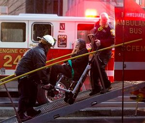 A woman is transported in a wheelchair onto an ambulance bus as people are evacuated from a smoke filled Metro subway tunnel in Washington, Monday, Jan. 12. (AP Photo/Jacquelyn Martin)