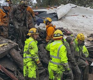 A mud-covered girl is pulled free by firefighters after they cut their way into her home. (Photo/Santa Barbara County Fire Dept.)