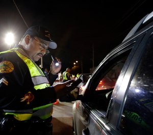 In this Thursday, Jan. 29, 2015 photo, Miami police officer Luis Ortiz looks at a driver's license he requested from a motorist during a drunk-driving checkpoint in Miami. (AP Photo/Lynne Sladky)